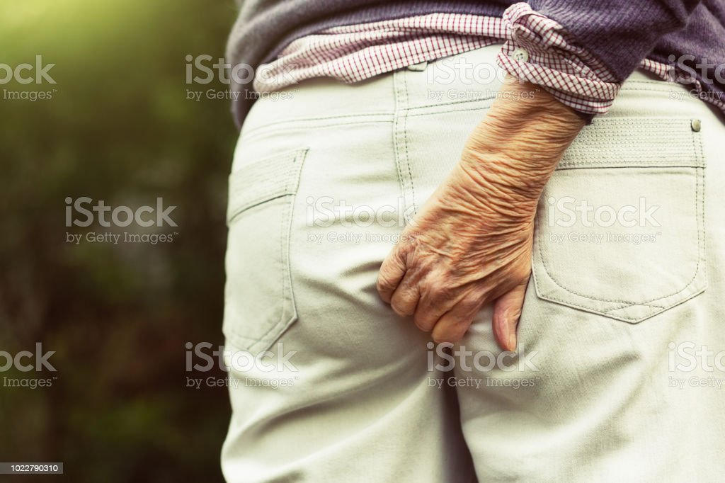 Senior hand scratching bottom through trousers stock photo