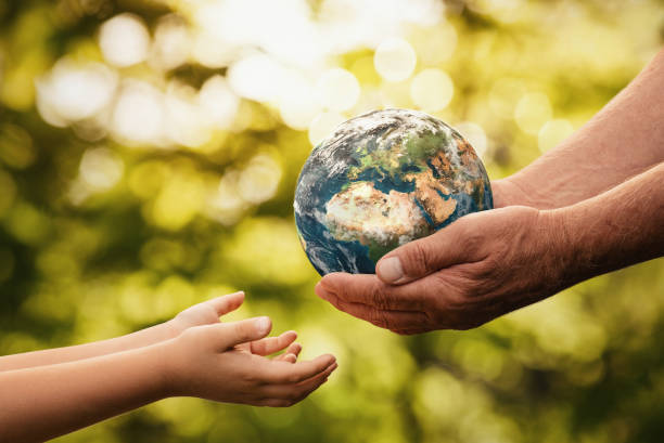 Senior hands giving small planet earth to a child Close up of senior hands giving small planet earth to a child over defocused green background with copy space planet earth stock pictures, royalty-free photos & images