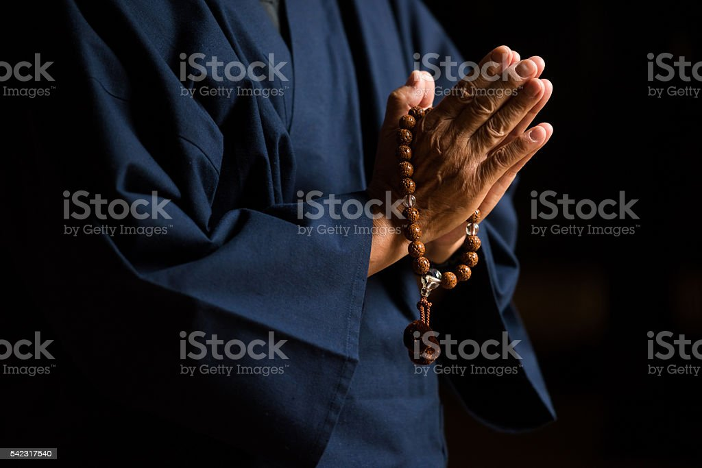 Senior hands with prayer beads stock photo
