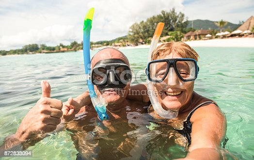 istock Senior happy couple taking selfie in tropical sea excursion with water camera - Boat trip snorkeling in exotic scenarios - Active retired elderly and fun concept around the world - Warm bright filter 872833094