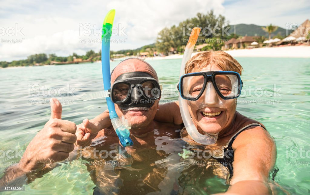 Senior pareja feliz tomando selfie en excursión de mar tropical con cámara de agua - paseo en barco en escenarios exóticos - activo jubilados mayor y divertido concepto del mundo - caliente filtro brillante - foto de stock