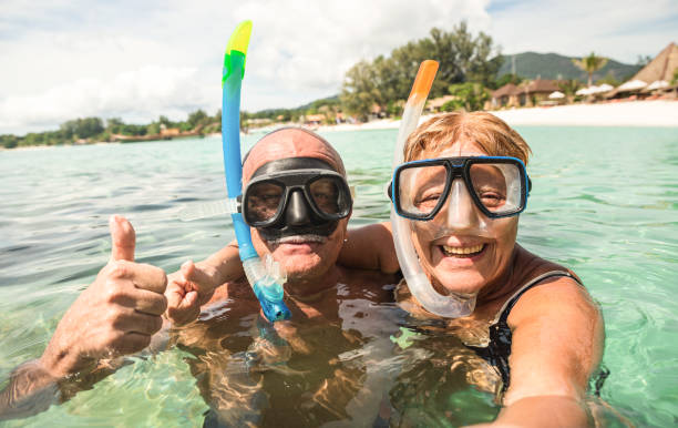 Senior happy couple taking selfie in tropical sea excursion with water camera - Boat trip snorkeling in exotic scenarios - Active retired elderly and fun concept around the world - Warm bright filter Senior happy couple taking selfie in tropical sea excursion with water camera - Boat trip snorkeling in exotic scenarios - Active retired elderly and fun concept around the world - Warm bright filter young at heart stock pictures, royalty-free photos & images