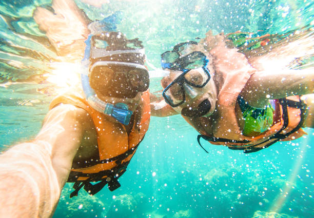 senior happy couple taking selfie in tropical sea excursion with water camera - boat trip snorkeling in exotic scenarios - active retired elderly and fun concept on scuba diving - warm vivid filter - underwater diving stock photos and pictures