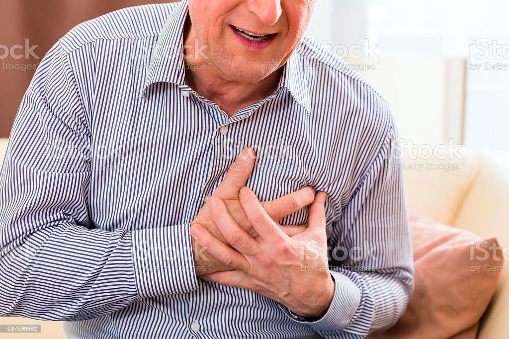 Senior having heart attack at home stock photo