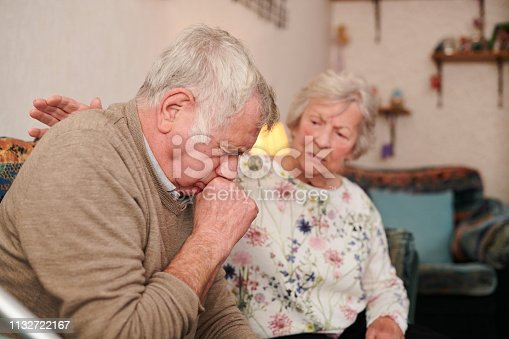 senior man with wife at home coughing badly