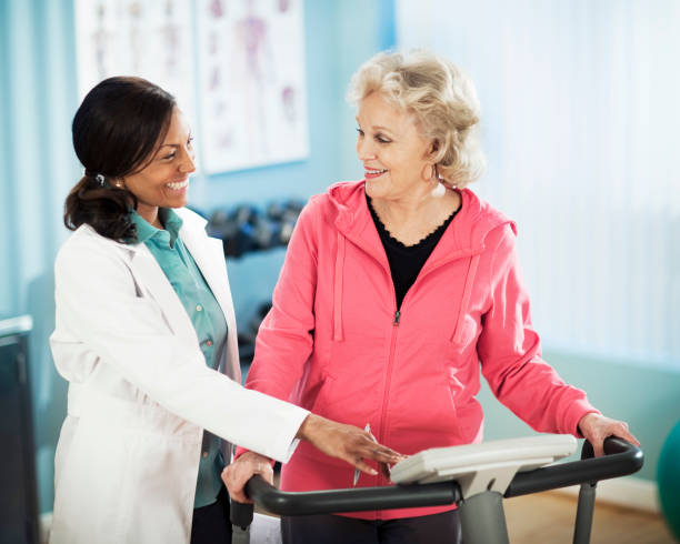 Senior Healthy LIfestyle Active senior woman exercising on treadmill with physical therapist. drug rehab stock pictures, royalty-free photos & images