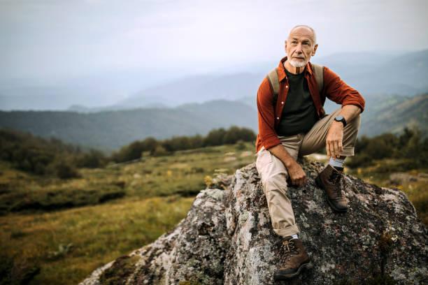 Senior hiker posing on the mountain rock stock photo