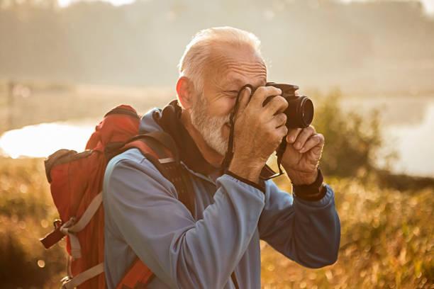senior hiker mit rucksack wandern in der nähe des sees fotografieren - senior bilder wasser stock-fotos und bilder