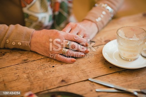 Close-up of an unrecognisable senior woman hands clasped on a table. She has multiple rings on different fingers.