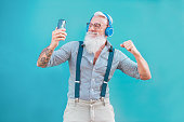 istock Senior hipster man using smartphone app for creating playlist music - Trendy tattoo guy having fun with mobile phone technology - Tech and joyful elderly lifestyle concept - Focus on his face 1141427212