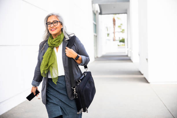 senior hispanic businesswoman walking down hallway - baby boomers stock pictures, royalty-free photos & images