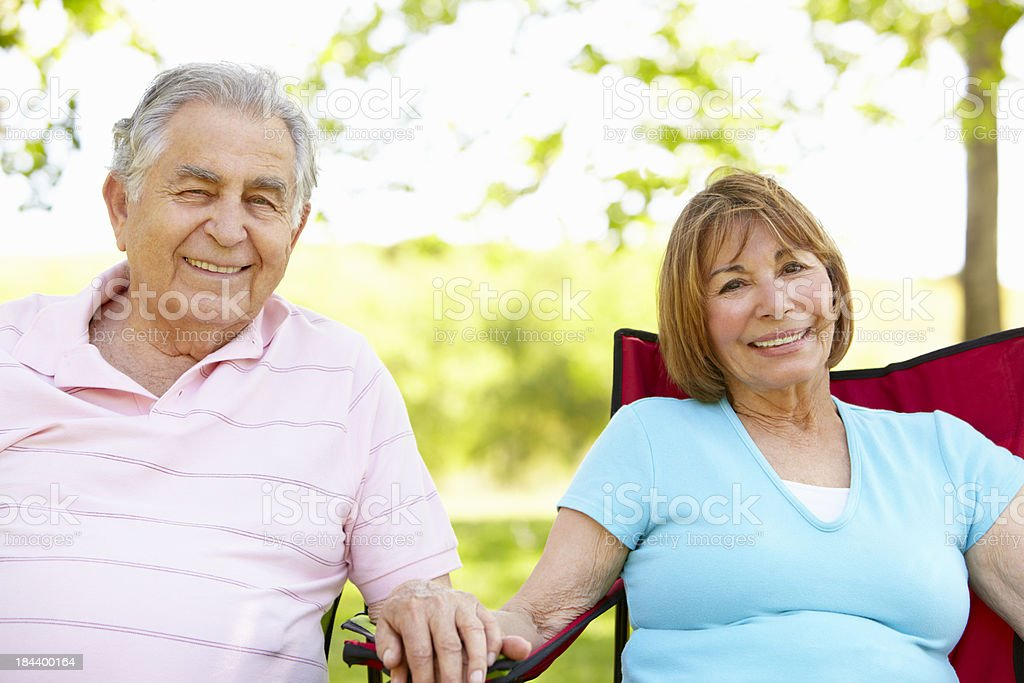 Senior Hispanic Couple Relaxing In Park royalty-free stock photo