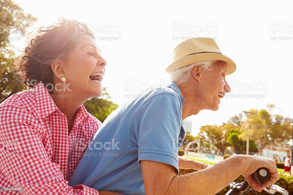 Senior Hispanic Couple Riding Bikes In Park stock photo