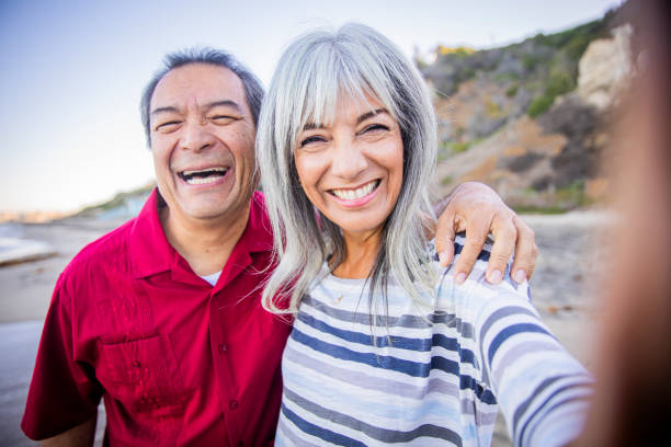 Senior Hispanic Couple Taking Selfie at the Beach A senior Hispanic Couple taking a selfie at the beach medicare stock pictures, royalty-free photos & images