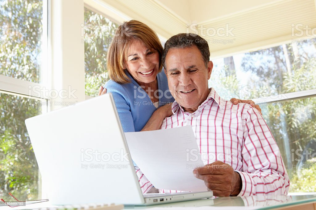 Senior Hispanic Couple Working In Home Office stock photo