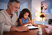 istock Senior Hispanic man at home with his young granddaughter using stylus and tablet computer 1094016478