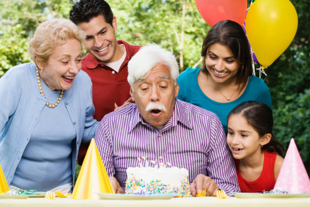 Senior Hispanic man blowing out birthday candles with family in park Senior Hispanic man blowing out birthday candles with family in park birthday wishes for daughter stock pictures, royalty-free photos & images