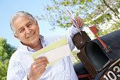 Senior Hispanic Man Checking Mailbox Holding Mail and Smiling at Camera