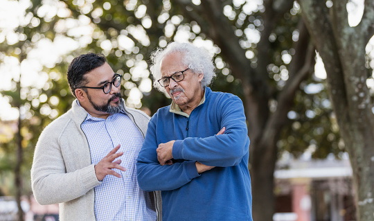 A senior Hispanic man in his 80s standing outdoors in a city park, conversing with his adult son, a mid adult man in his 30s. The older man is frowning with is arms crossed as the younger one talks.