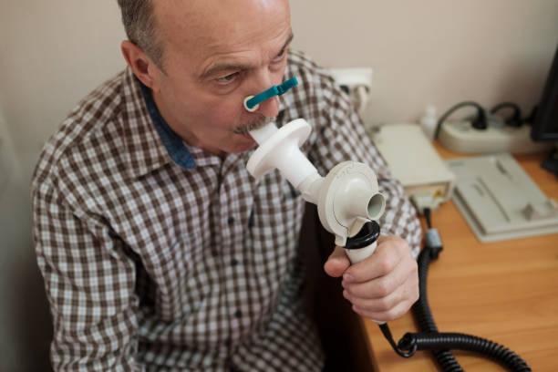 Senior hispanic man man testing breathing function by spirometry stock photo