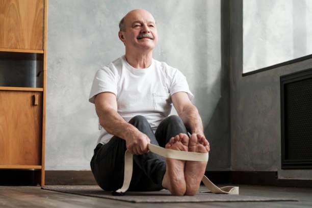 Senior hispanic man sitting in paschimottanasana or Intense Dorsal Stretch pose stock photo