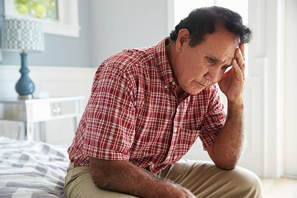 Senior hispânica homem sentado na cama, que sofre com Depressão - foto de acervo