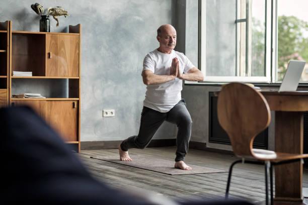 Senior hispanic man standing in warrior yoga pose variation stock photo