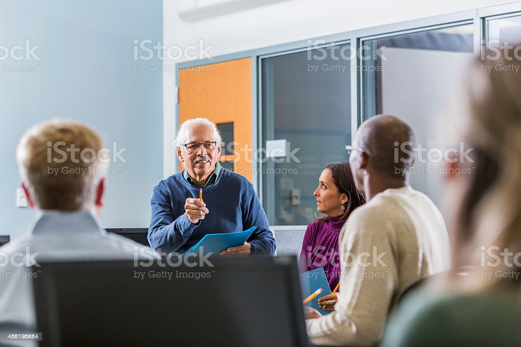 Senior Hispanic man teaching adult students stock photo