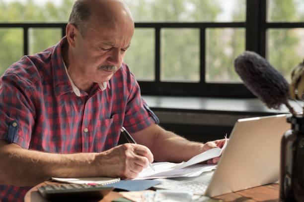 Senior hispanic man using calculator and calculate bills stock photo