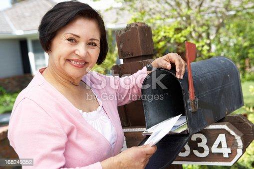 istock Senior Hispanic Woman Checking Mailbox 168249352