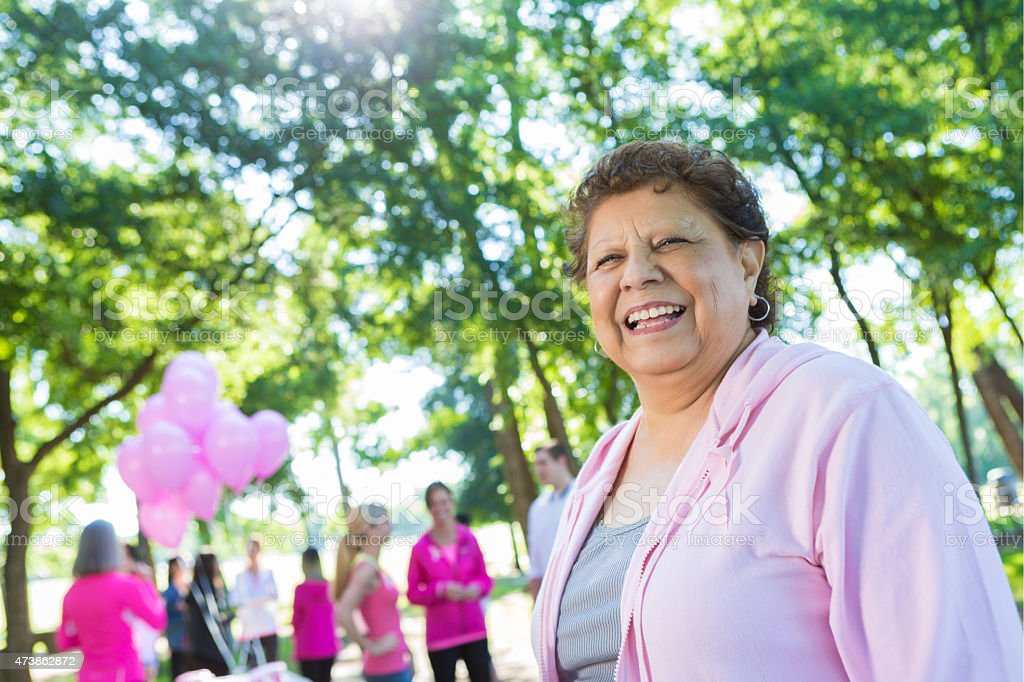 Senior Hispanic woman is survivor at breast cancer awareness race stock photo