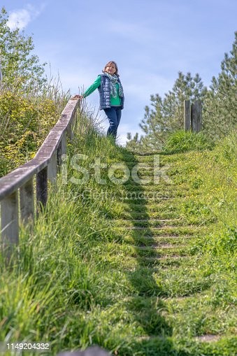 Senior Hispanic woman portrait standing at top of steps in Welsh countryside