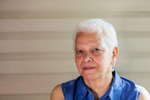 Senior-Hispanic Frau sitzt auf Veranda, Ernst – Foto