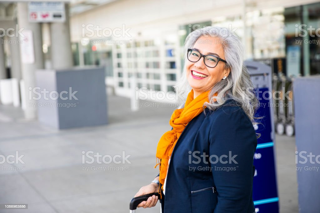 Senior Hispanic Woman waiting outside the airport stock photo