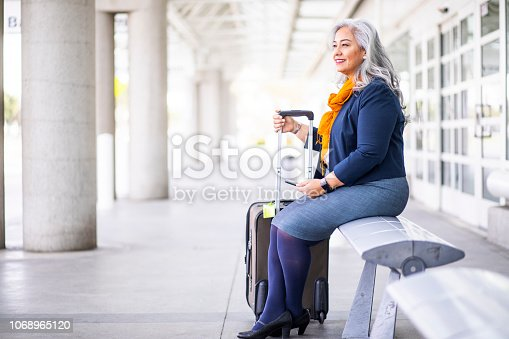 A Senior Hispanic Woman waits on a bench outside the airport