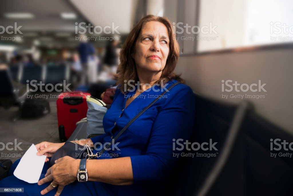 Senior Hispanic Woman Waiting to Travel in Airport royalty-free stock photo