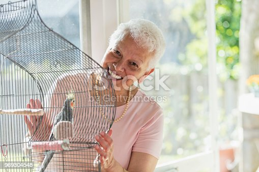 A senior Hispanic woman in her 60s playing with her pet bird, a cockatiel, in a birdcage. She is smiling and looking at the camera.