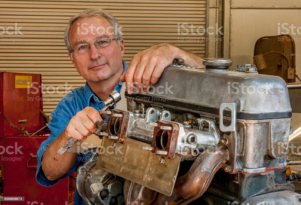 Senior Hobbyist Rebuilding an Automobile Engine stock photo