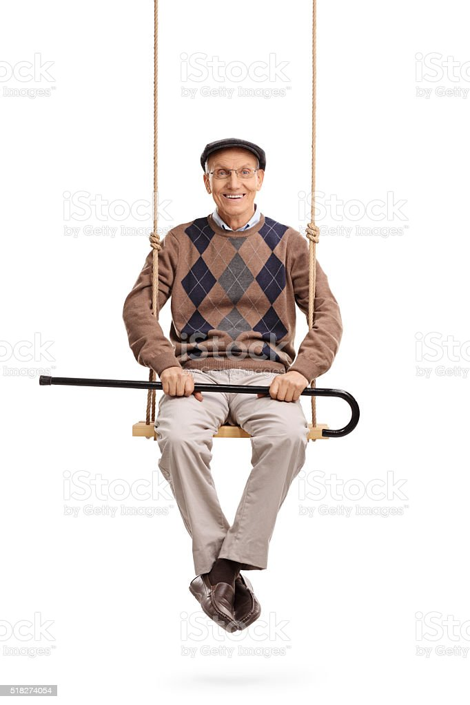 Senior holding his cane and sitting on a swing stock photo
