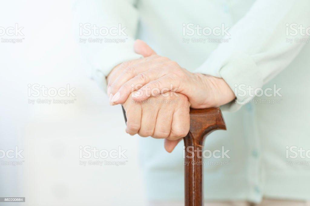 Senior holding wood cane stock photo