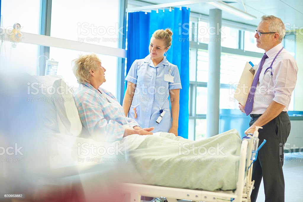 senior hospital patient chatting to doc and nurse stock photo