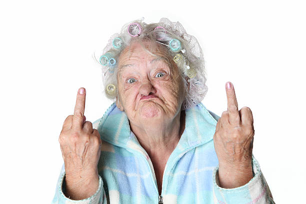 Senior Humor: cranky woman making faces and flipping the bird. stock photo
