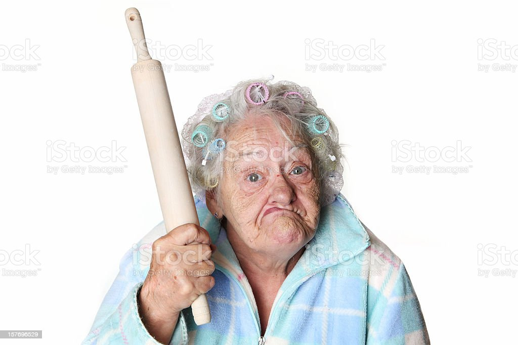 Senior Humor: cranky woman making faces and holding rolling pin royalty-free stock photo