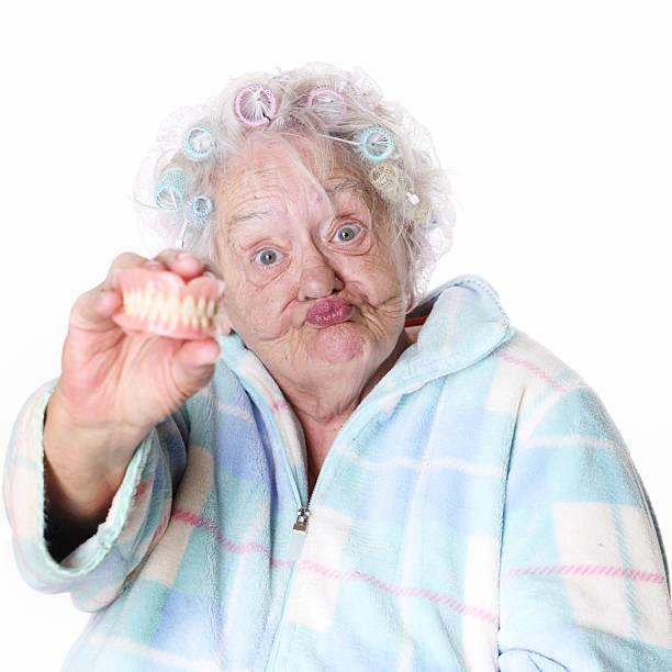 Senior humour: Femme tenant false dents - Photo