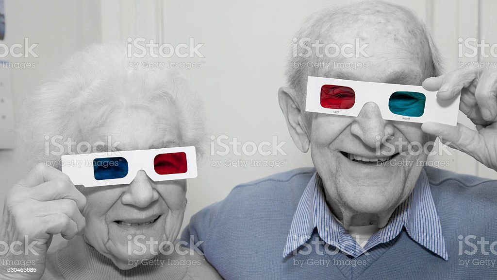 Senior husband and wife having fun with 3D glasses stock photo