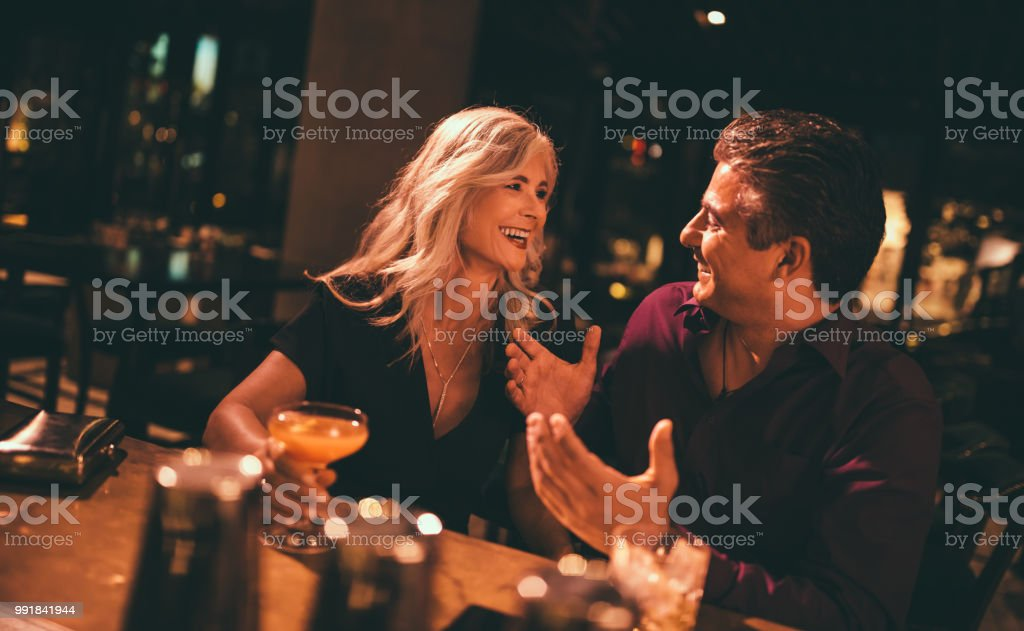Senior husband and wife laughing and having drinks at bar stock photo