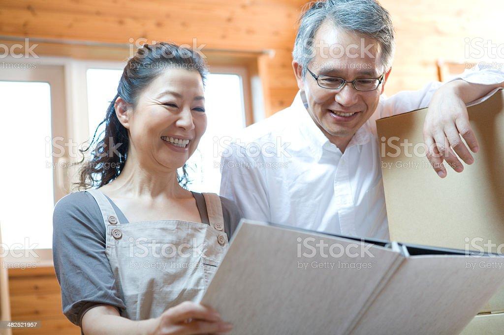 Senior husband and wife looking photo album stock photo