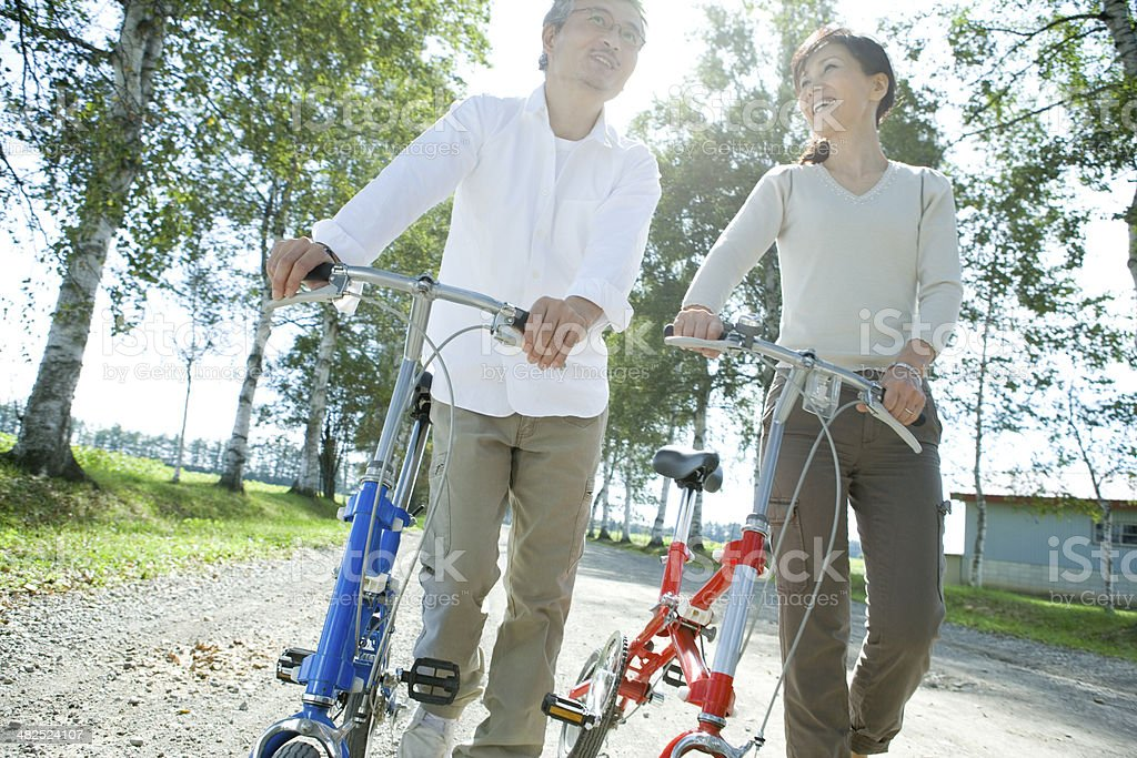 Senior husband and wife pushing their bicycle stock photo