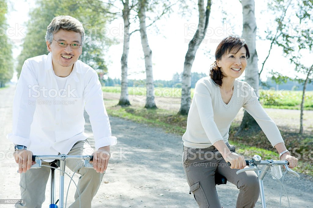 Senior husband and wife riding on bicycle stock photo