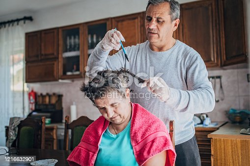 Senior husband dyes his wife's hair at home as she can't go to the salon because of coronavirus lockdown.